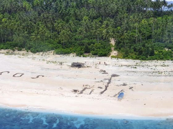 """En esta foto proporcionada por la Fuerza de Defensa de Australia, tres hombres se paran en la playa de la isla Pikelot en los Estados Federados de Micronesia el domingo 2 de agosto de 2020, donde se los encuentra seguros y saludables después de estar desaparecidos durante tres días. Los hombres desaparecieron en el archipiélago de Micronesia, al este de Filipinas, durante casi tres días cuando su señal """"SOS"""" fue detectada por buscadores en aviones australianos y estadounidenses, dijo el departamento de defensa australiano. (Fuerza de Defensa Australiana vía AP)"""